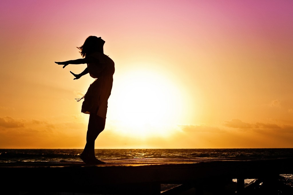 A woman throws her arms back in front of a sunset, only her silhouette is seen and a beach.