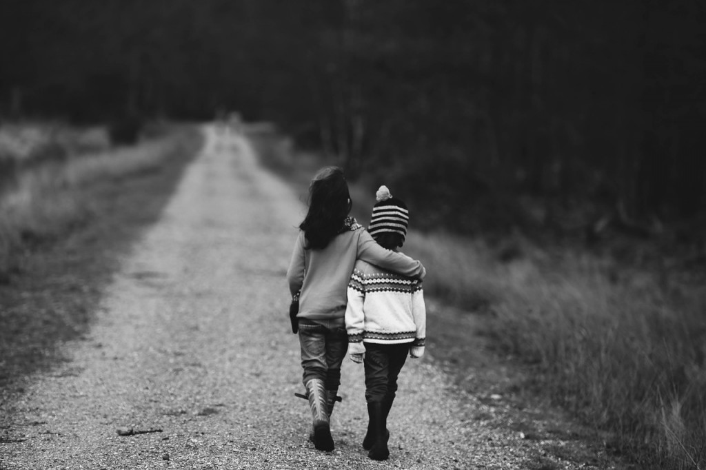 A black and white pictures of siblings walking down a trail.