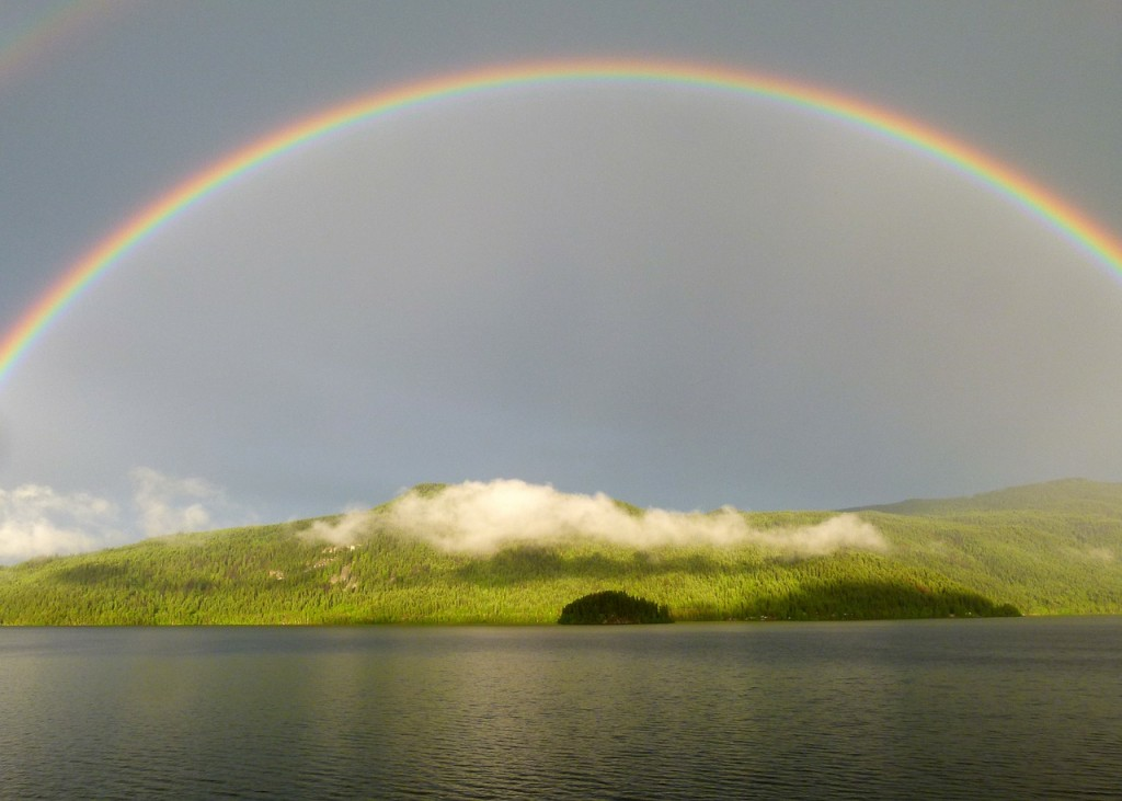 Hey all. A rainbow in the sky over a hill and water.