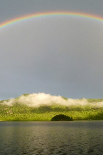A rainbow over an island by the water.