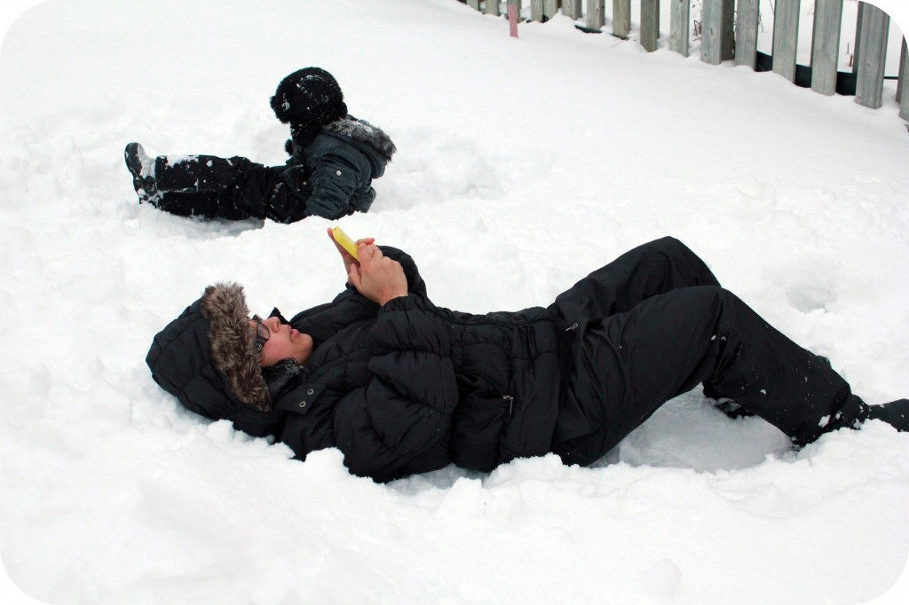 Snowmageddon. A little girl plays in the snow while mother tweets on her phone on the ground.