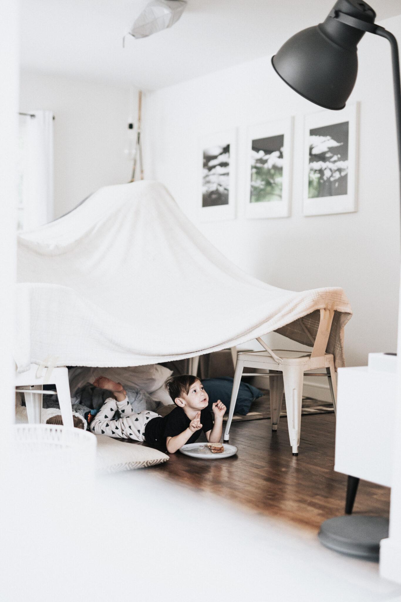 A little boy plays under a living room fort, eating a sandwich.