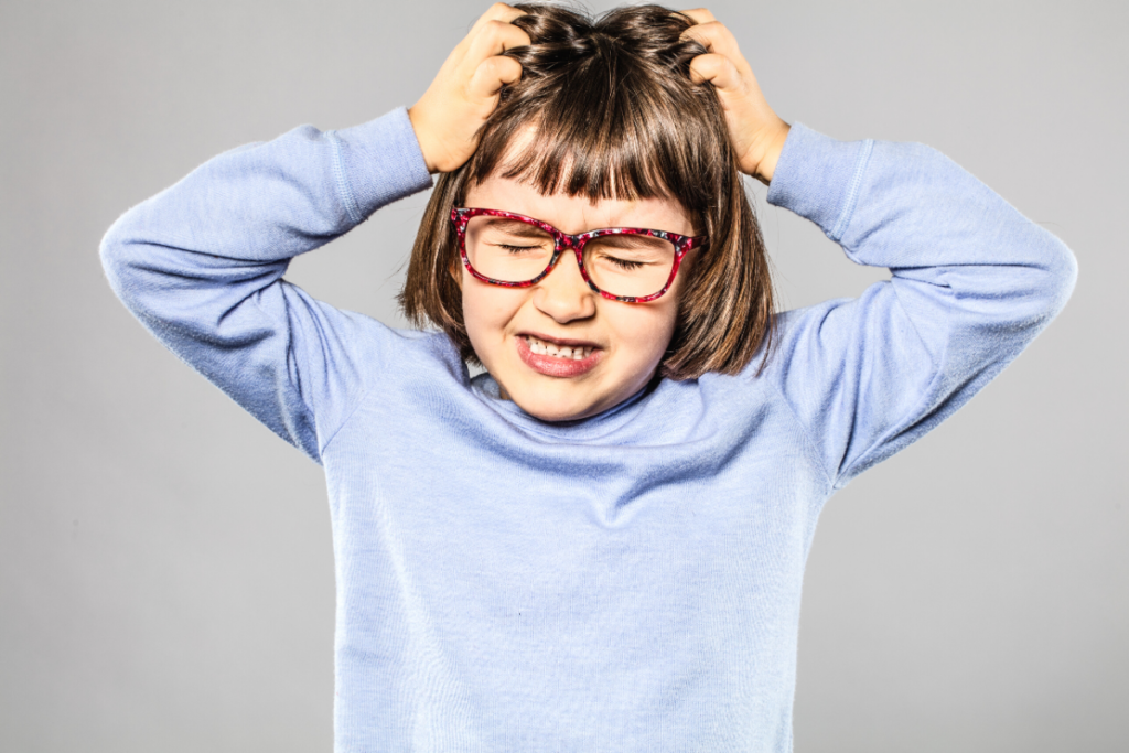 A little girl with glasses winces, closes her eyes, and scratches her head. This article covers 6 Tips on How to Prevent Head Lice.