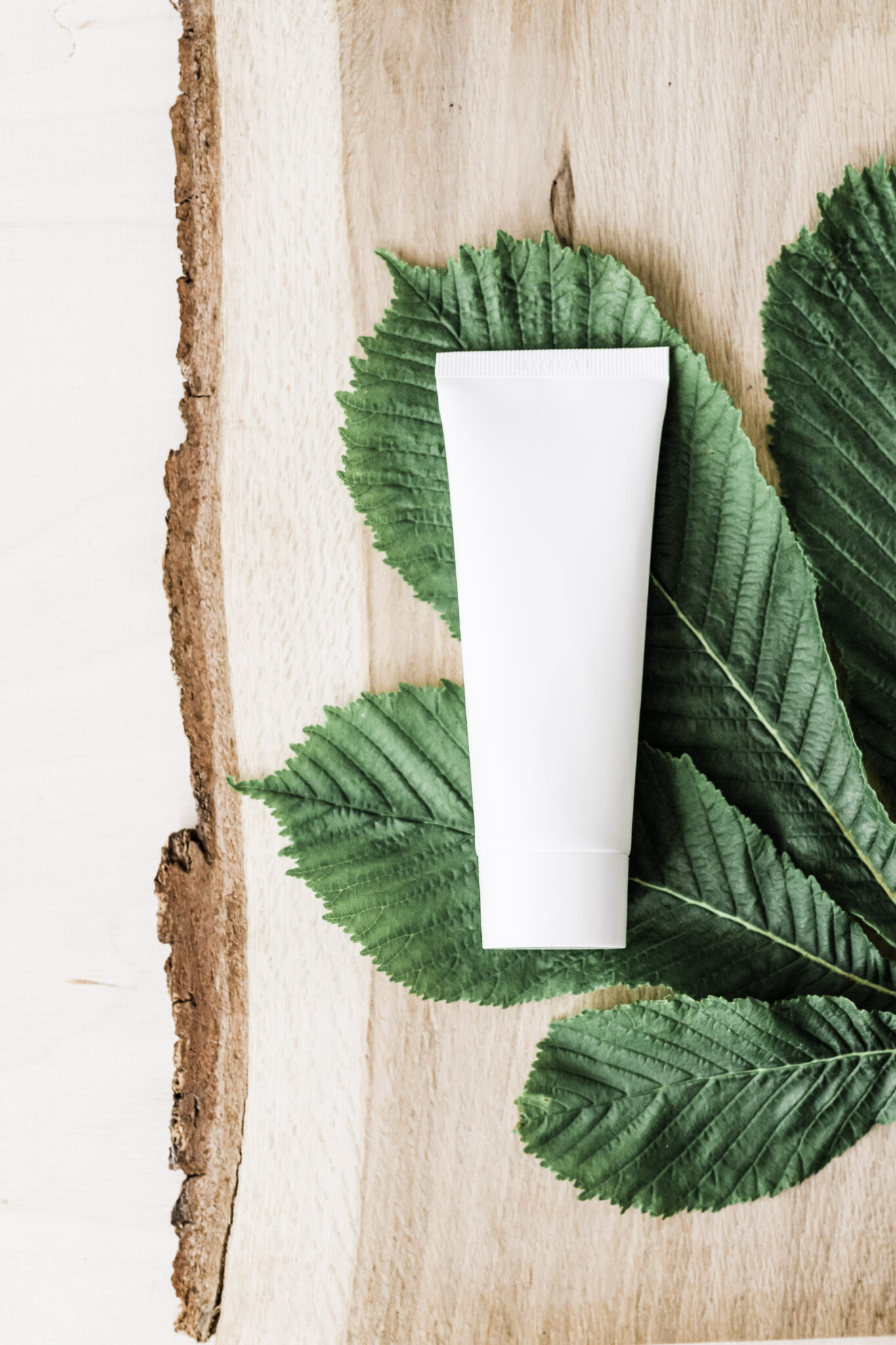 A white shampoo bottle lies on green leaves on a wooden live edge board.