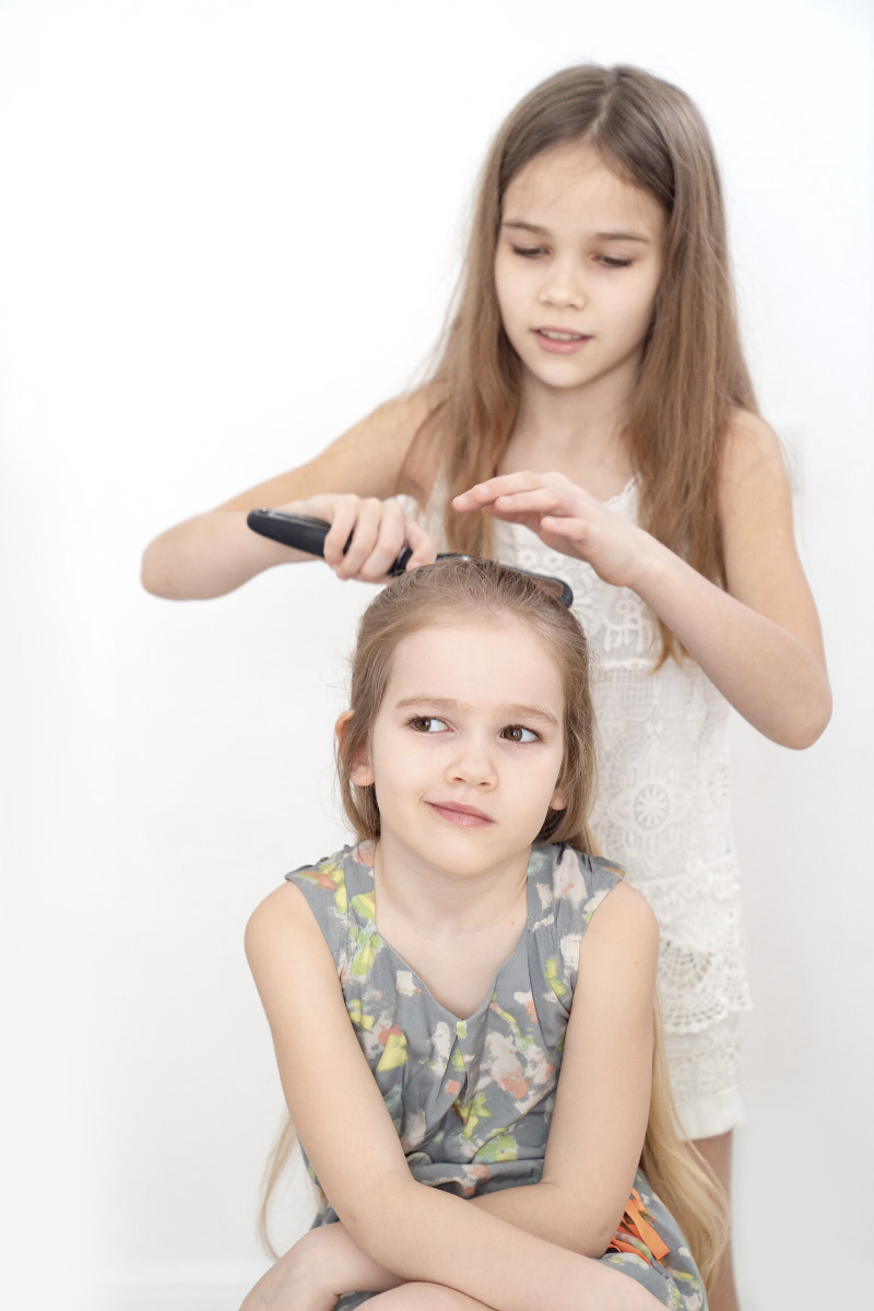 Two girls stand together and the older one brushes the younger girl's hair with a brush.