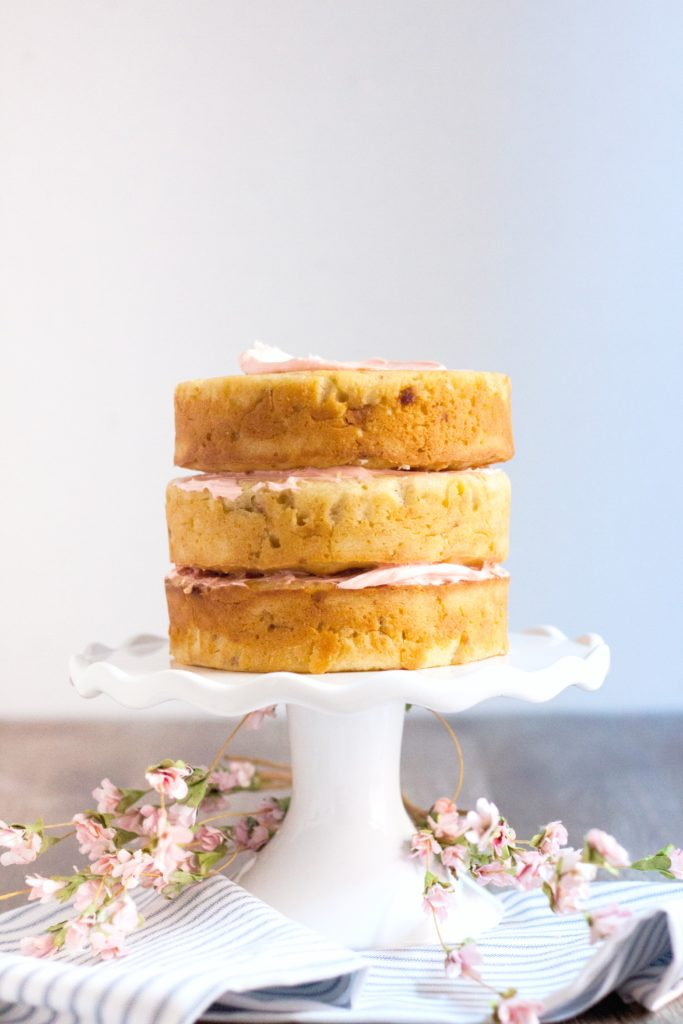Cake stand with 3 stacked cakes beginning to get iced.