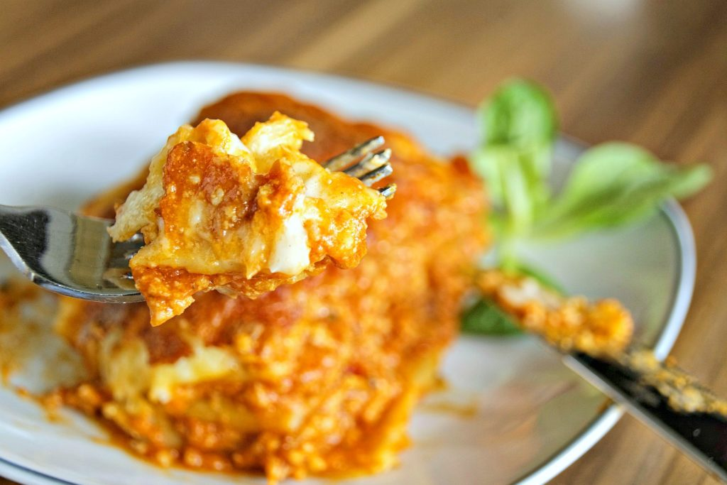 A fork is picking up a bite of lasagna and a piece of lasagna is shown.