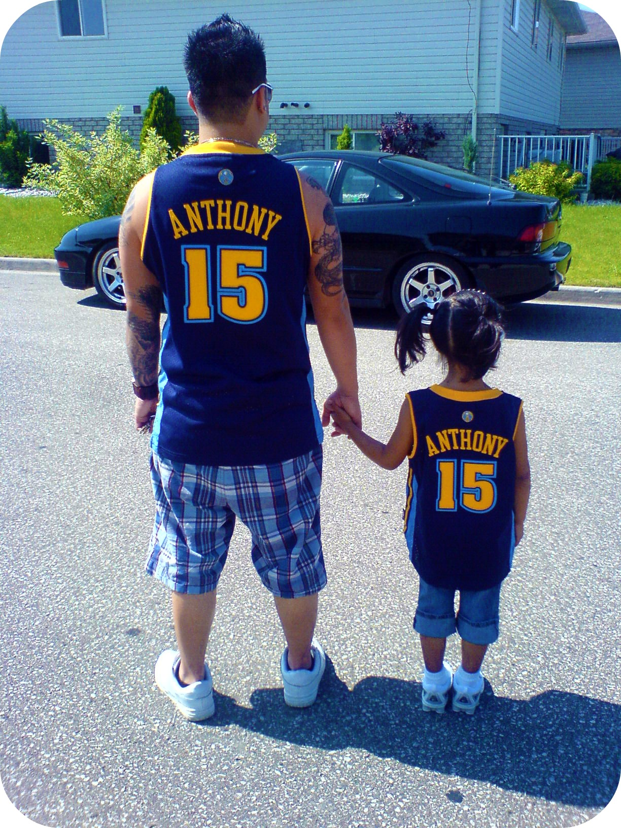 A man wears an Anthony basketball jersey and he holds hand with a tiny little girl wearing the same journey. Father and daughter. Blessed to have this man.