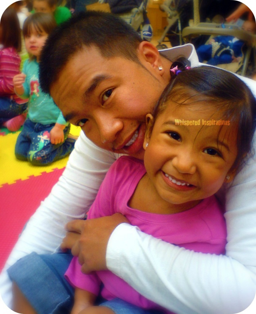 A dad hugs a little girl while sitting on the floor. She smiles into the camera.