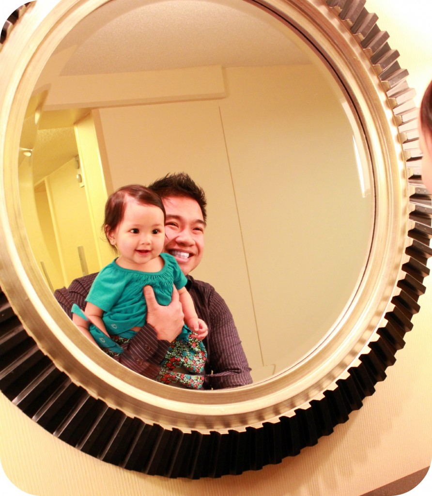 Dad and baby look at their reflections in the mirror. They both smile.