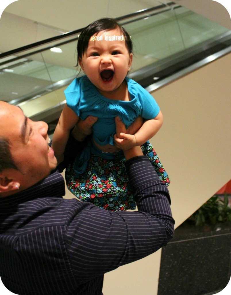 A little girl is being held up by her Dad and she opens her mouth wide in delight.