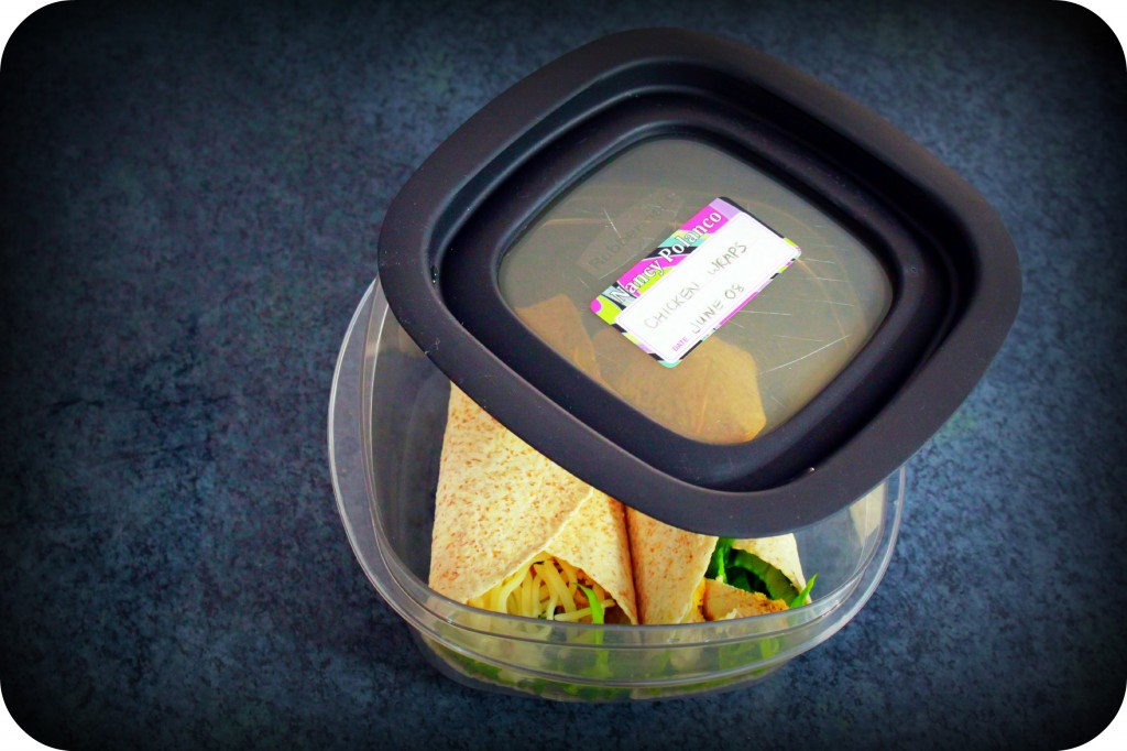 A halfway closed Tupperware is shown with chicken wraps inside. A label is affixed to the lid.