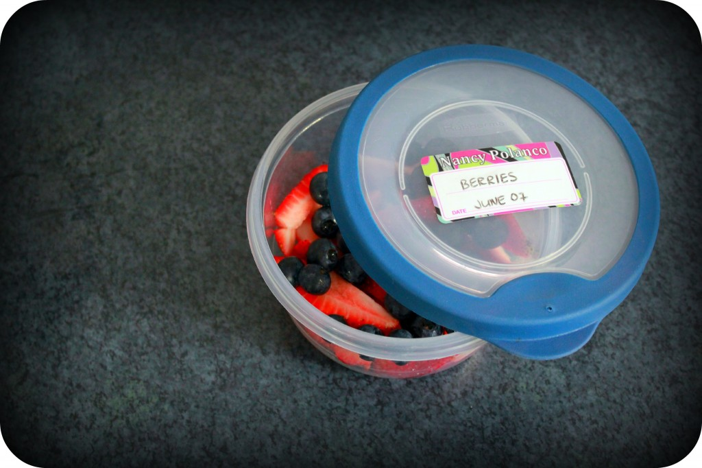 A halfway open tupperware with berries and an label with with an expiry date is on the lid.