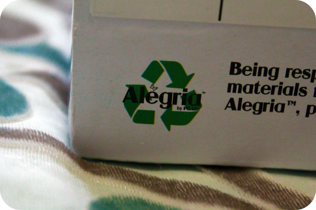 A close up of an Alegria shoebox is shown with a recycling symbol.