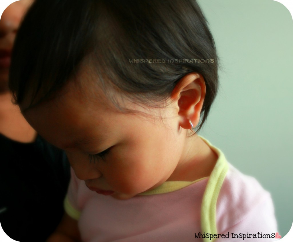 A Baby Looks Down And Shows Off Her Hoop Earrings