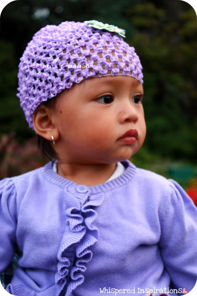 A Baby Is Dressed In Purple And Looking To Her Side An Earring