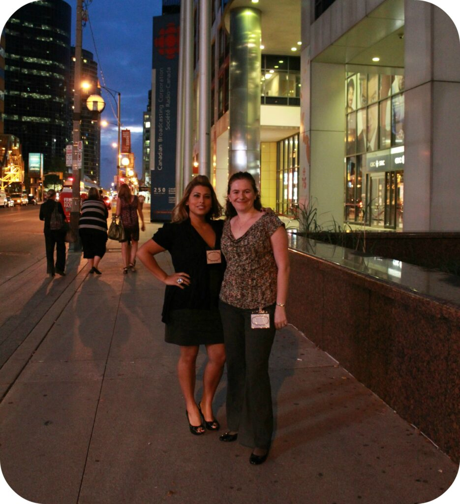 Two women stand together on the streets of Toronto.