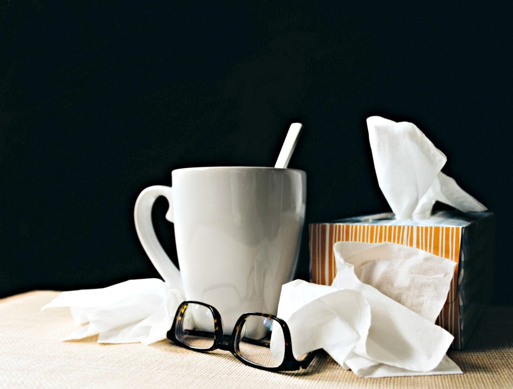 A cup with tea, tissues and a pair of glasses. Cold and Flu season is here.