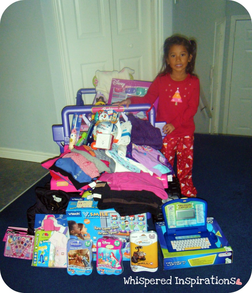 A little girl stands in front of toy Jeep and it is filled with gifts and she is surrounded by gifts.