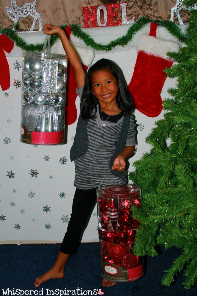 A little girl holds buckets of ornaments for the Christmas tree.