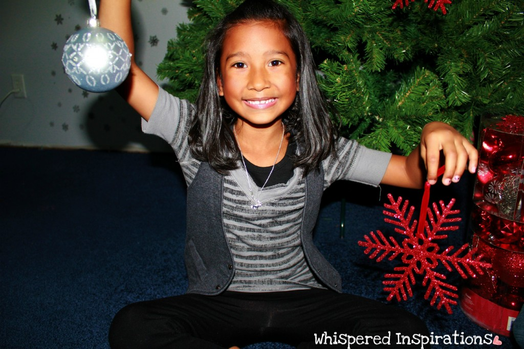 Little girl holds ornaments.