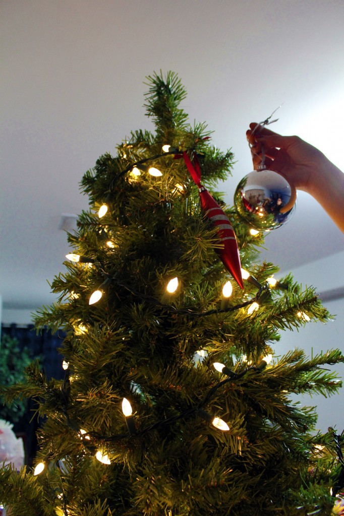 A woman places an ornament at the top of the tree.