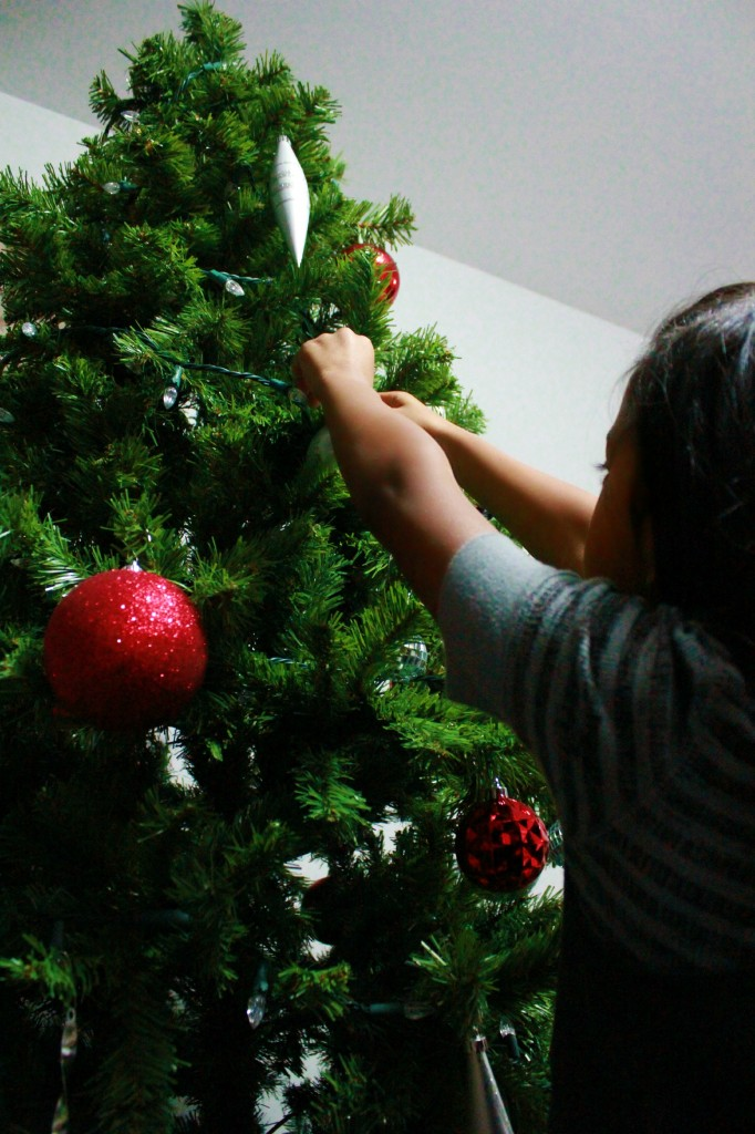 Little girl places ornaments on Christmas tree.