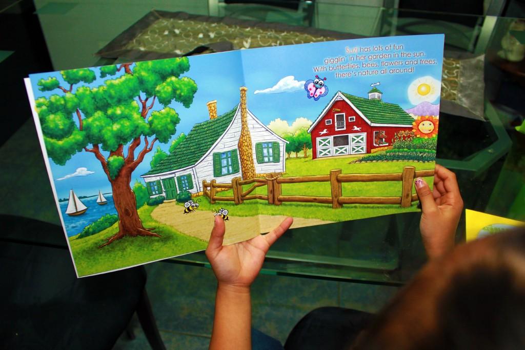 A little girl holds a book open.