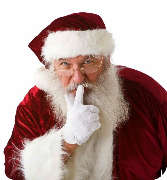 Santa Claus looking at you and putting his finger in a shh motion on his lips.