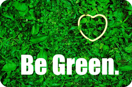 A gold heart is placed on green grass and the words 'Be Green' is written across.