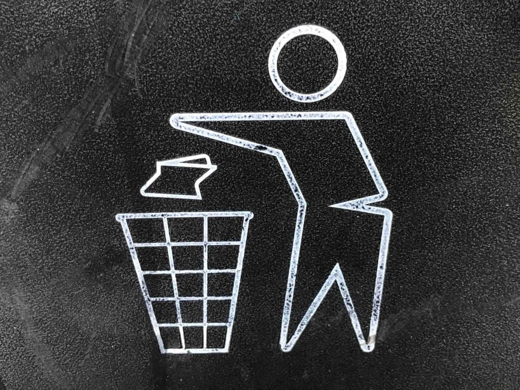 Sign showing a person placing garbage in trash bin.