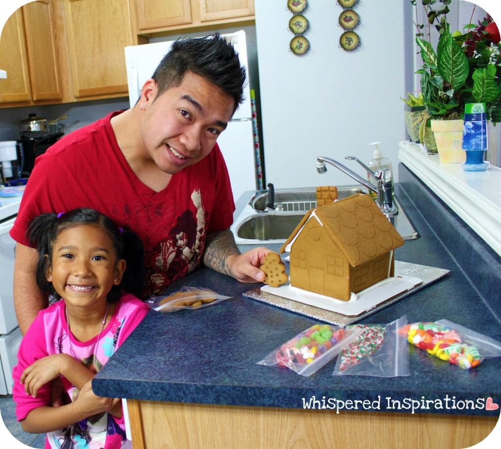 A little girl and her dad make a gingerbread house in the kitchen.
