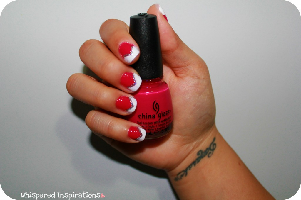 A hand is holding a China Glaze pink nail polish and showing off a pink and white manicure.