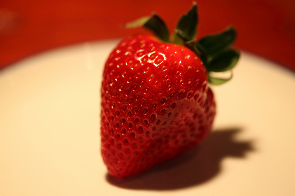 A strawberry on a plate.