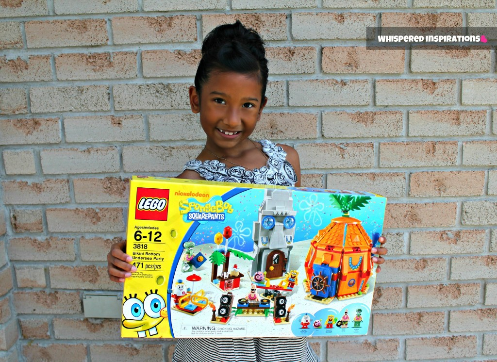 Little girl stands in front of a brick wall holding a large LEGO Spongebob Squarepants set.