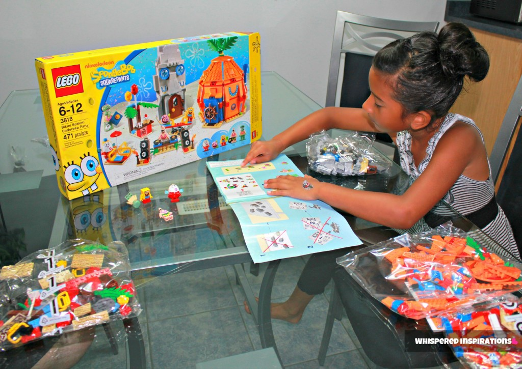Gabby sits at a glass table and looks at the guide to start building the Spongebob LEGO set.