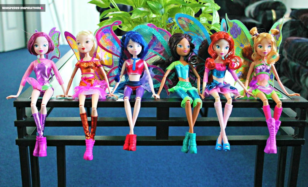 Six Winx Dolls sit on the edge of a coffee table.