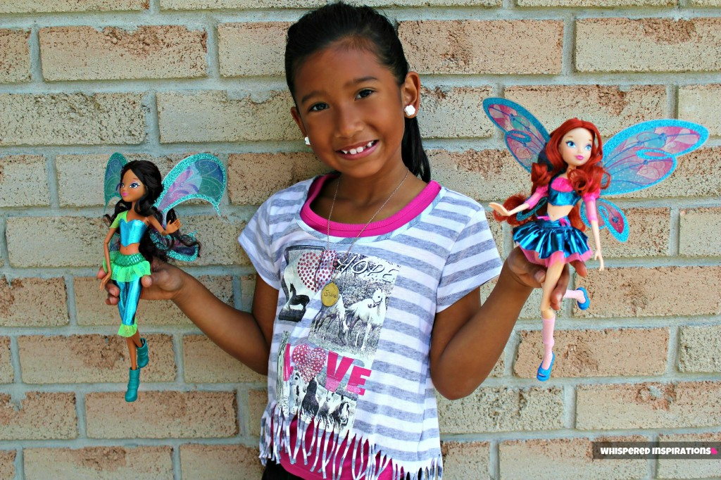 Gabby smiling against a brick wall and holding two Winx dolls.