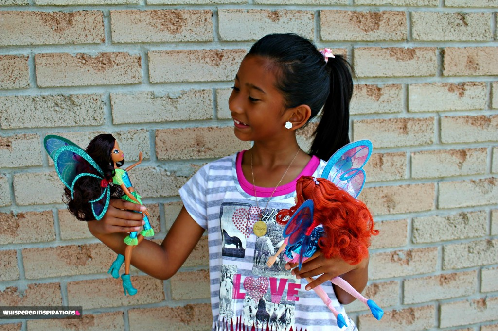 Gabby looking down at her two dolls and smiling.