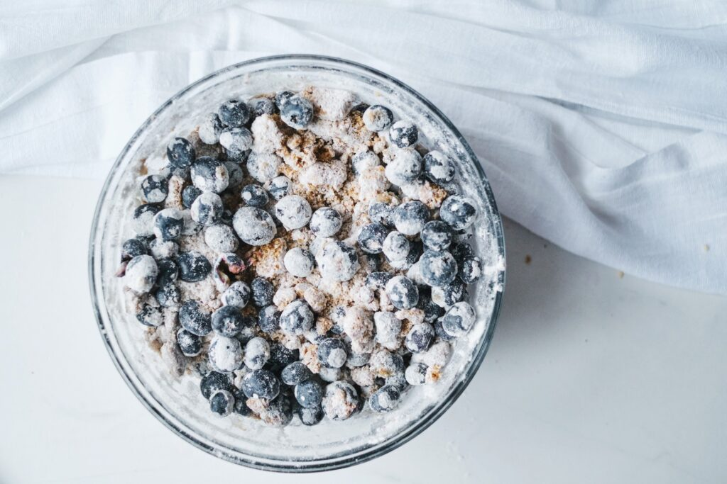 Folding the blueberries in to the filling ingredients. A bowl is shown with all dusted blueberries.