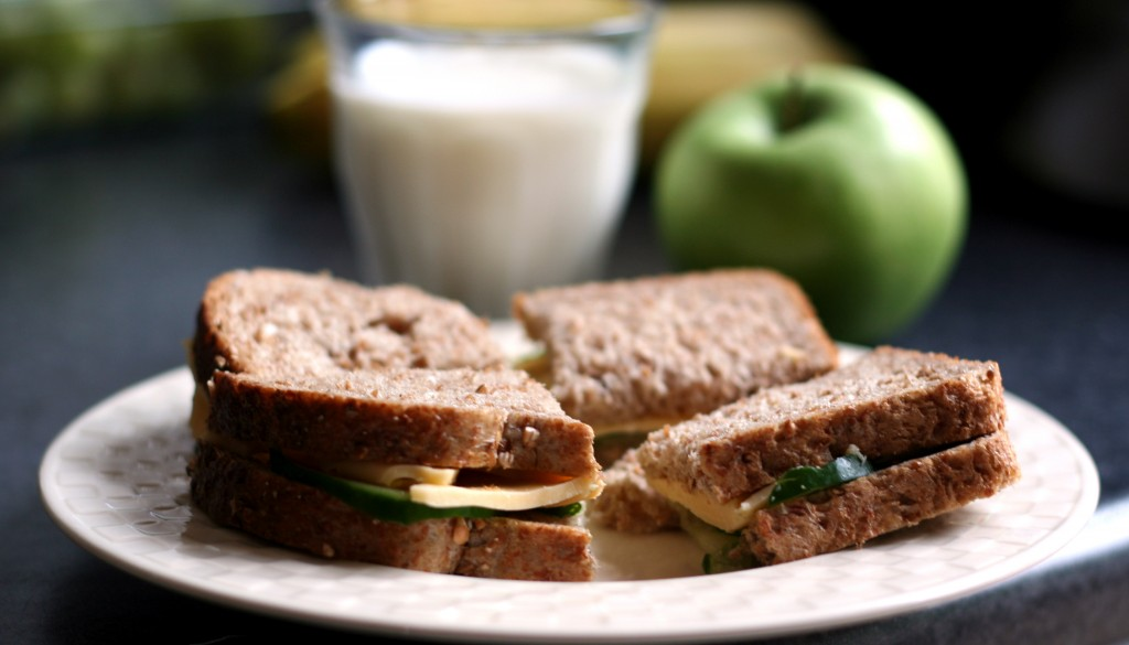 Sandwich is served with a glass of milk and green apple.