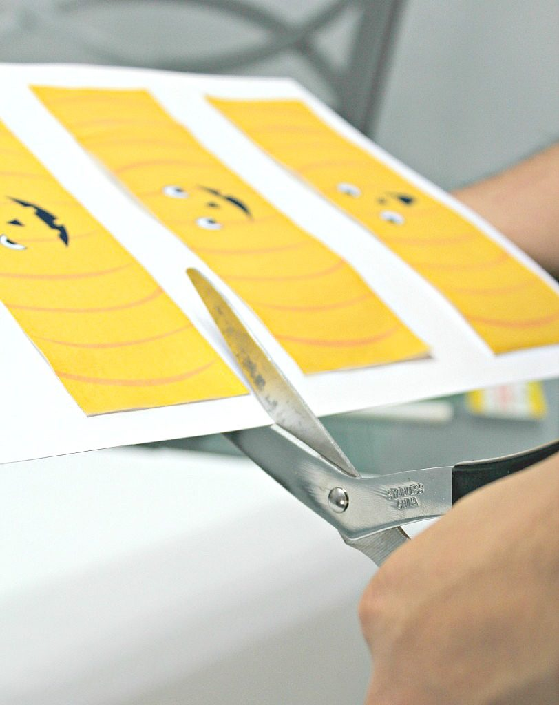 A hand is shown cutting the printable after it's been pasted onto thick paper.