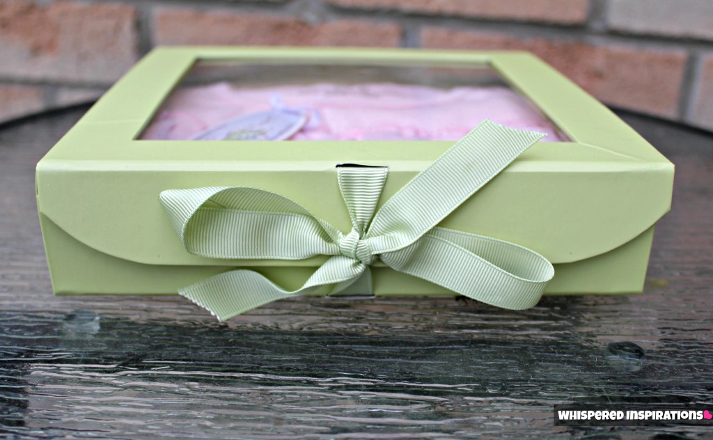 The organic dress in a pretty green box held closed by a green ribbon.