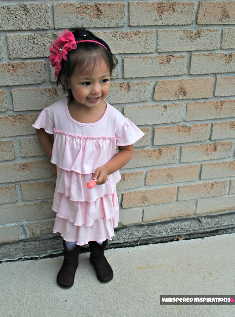 Little girl stands outside posing in front of a brick wall and shows off her dress.