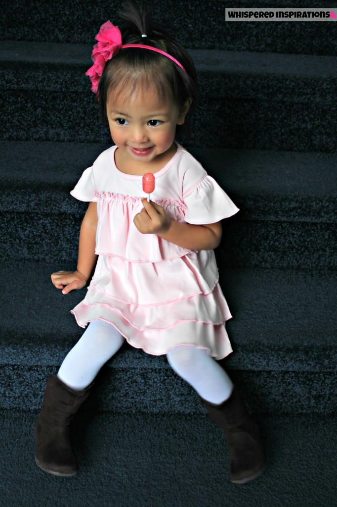 Little girl wears a pale pink organic dress with tights and boots while holding a lollipop.
