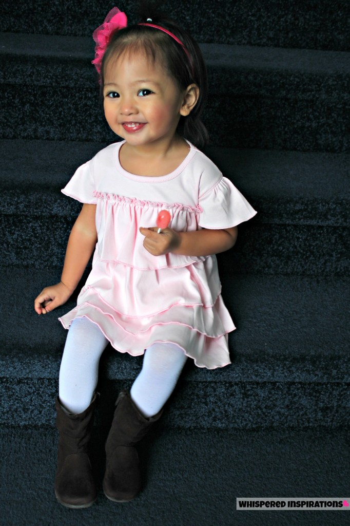 Little girl sits on the stairs while holding a lollipop and smiling.