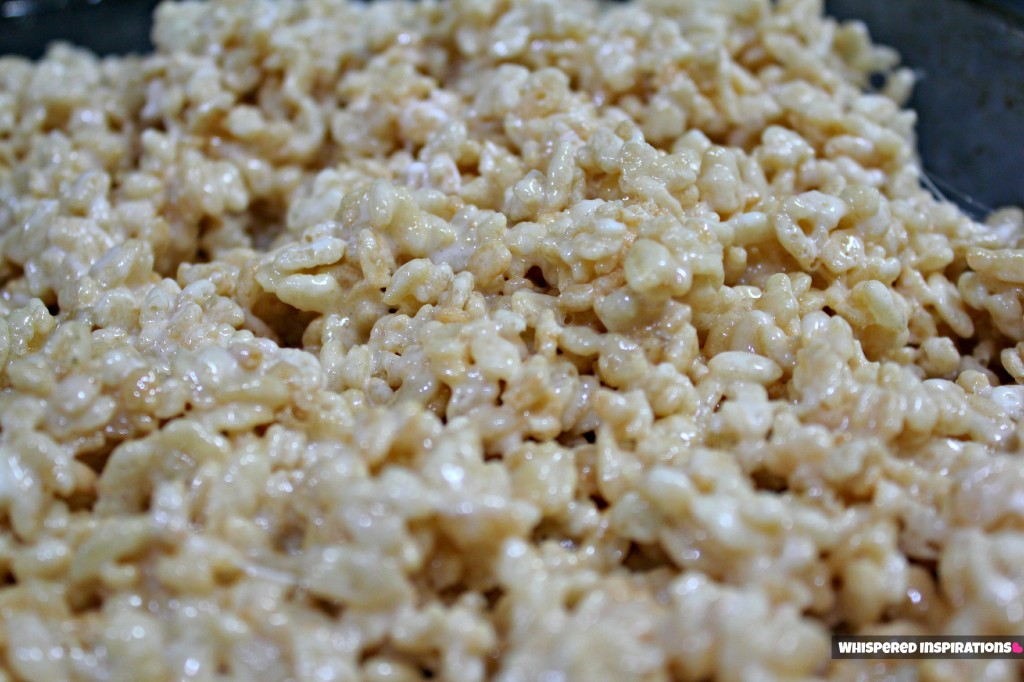 Rice Krispies all mixed up and ready to be placed in a pan.