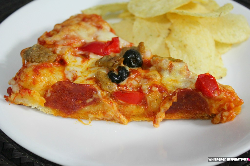A slice of pizza and potato chips are shown on a plate.
