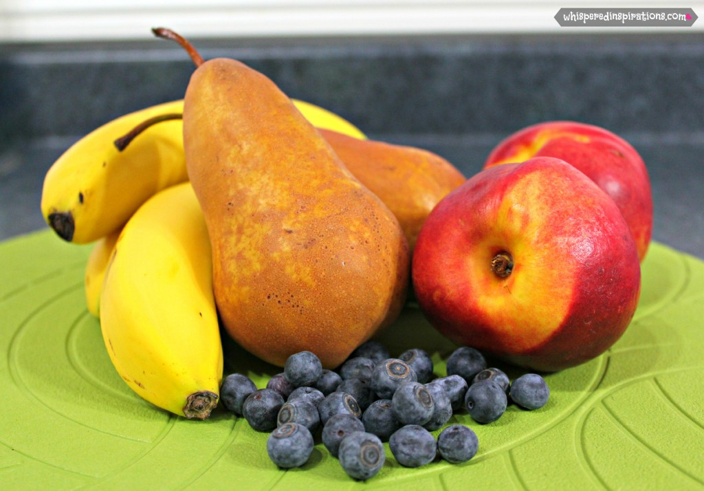 Bananas, pears, peaches, and blueberries are shown and ready to be made into puree.