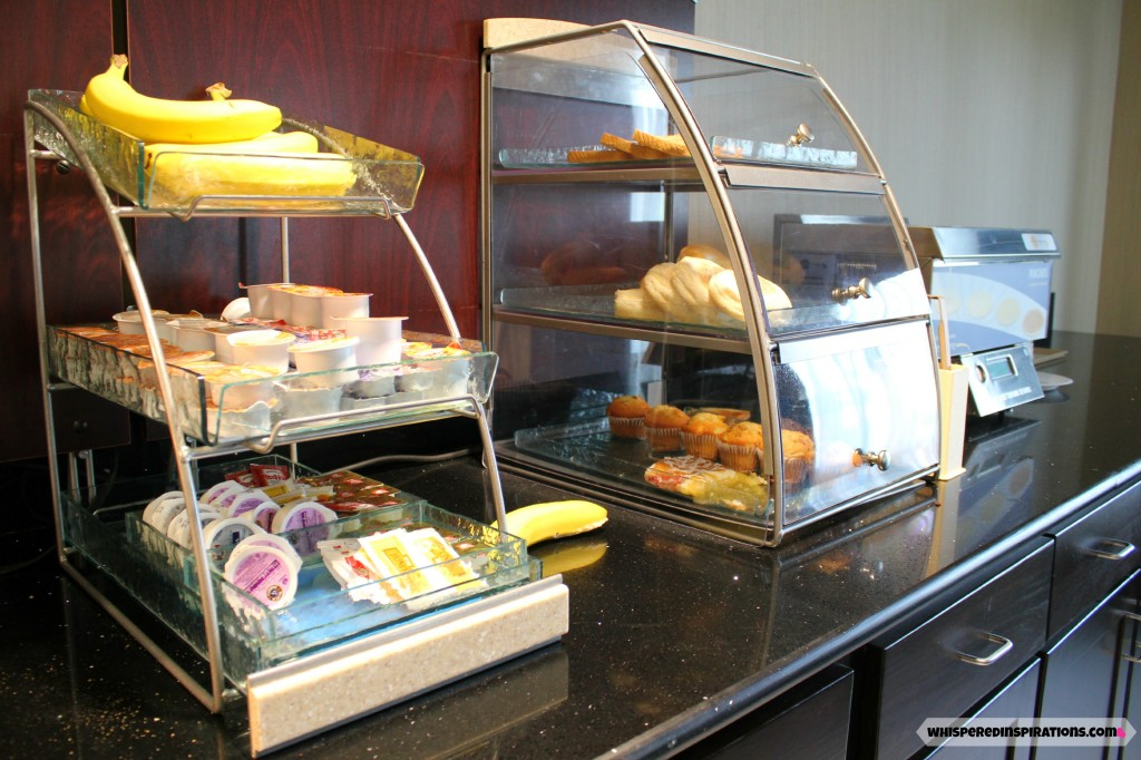 The Holiday Inn Express breakfast area, bananas, pastries, and jams are stocked for guest to enjoy.